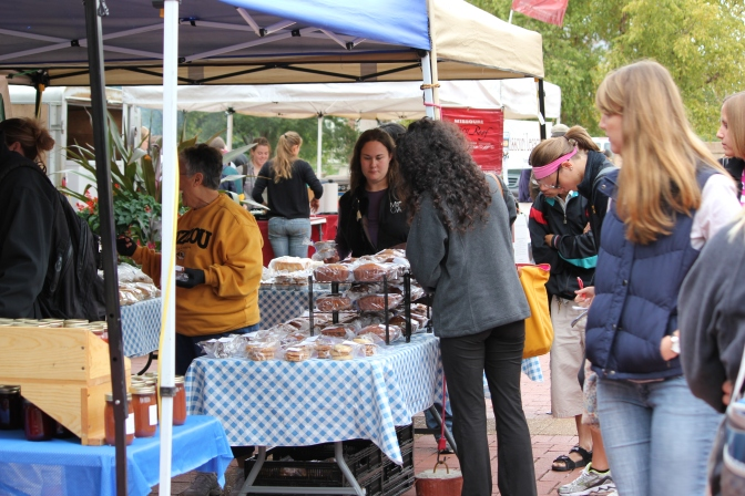 Students browse through baked goods at Grandma Barb's stand during the Campus Farmer's Market on Lowry Mall.